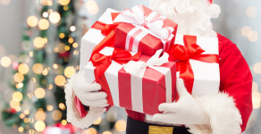 christmas, holidays and people concept - close up of santa claus with gift box over tree lights background